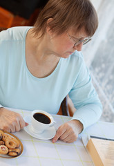 Elderly woman having coffee with cookies