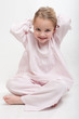 Little girl in her pajamas arranging her hair