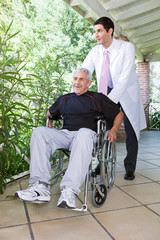 Elderly man on a wheel chair with a nurse