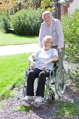 Senior man pushing his wife on a wheelchair