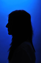 Girl silhouette over blue background.