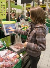 enfant qui pèse des fruits dans un supermarché