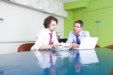 Two businessmen working in conference room