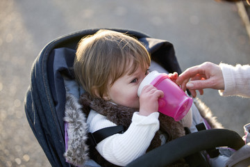 A baby girl drinking from a cup in her buggy
