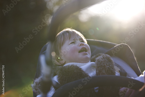 A baby girl crying in her buggy