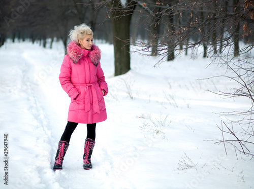 beautiful girl in a pink jacket in the winter against the backdr
