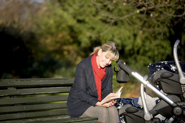 A mother sitting on a bench, reading a book