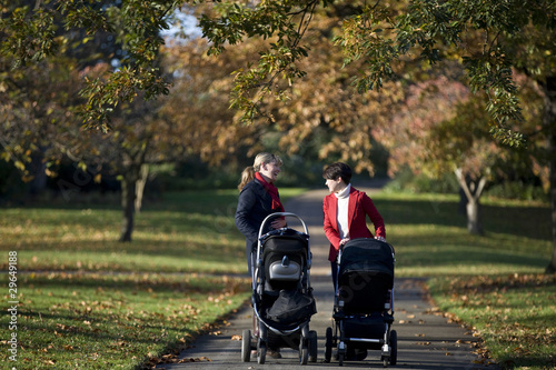 Two mothers pushing their buggies in the park, laughing