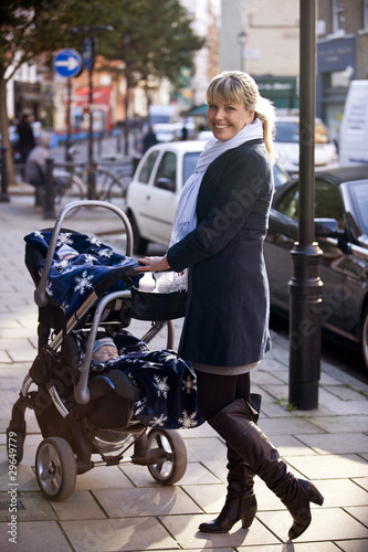 A mother with a buggy standing in the street, smiling