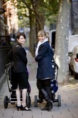 Two mothers standing with buggies in the street, smiling