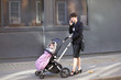 A mother pushing a buggy, talking on her mobile phone