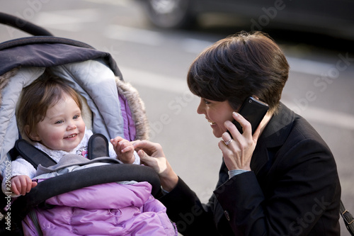 A mother smiling at her baby, talking on her mobile phone