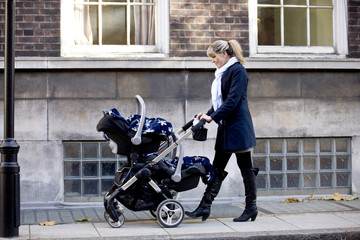 A mother pushing a double buggy in the street