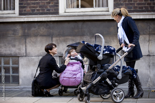 Two mothers with buggies meeting in the street