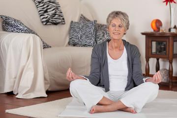 ältere frau macht yoga zuhause
