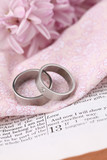 Bible open to 1 Corinthians 13 and wedding rings poster
