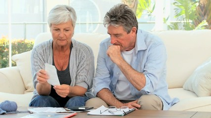 Mature couple calculating their bills at home