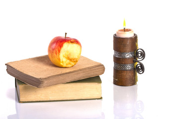 vintage books, apple and a candle
