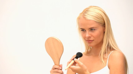 Blond woman putting on her make up against a white background
