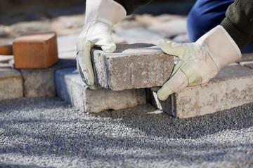 handwerker verlegt steine auf dem hof