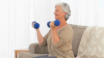 Elderly woman doing exercises om the sofa