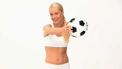 Cut blonde woman playing with a soccer ball