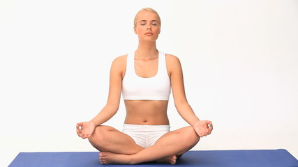 Pretty blond woman doing yoga against a white background