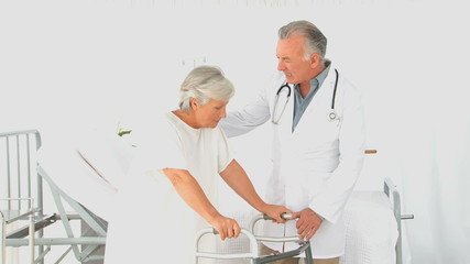 A doctor helping an elderly woman to do exercises