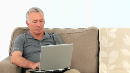 Elderly businessman working on his computer on his sofa
