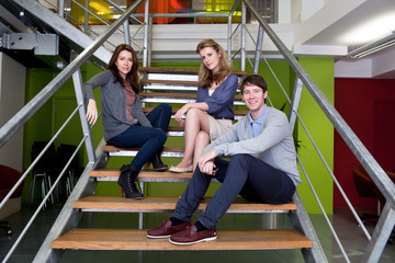 Man and two women sitting on stairs in office