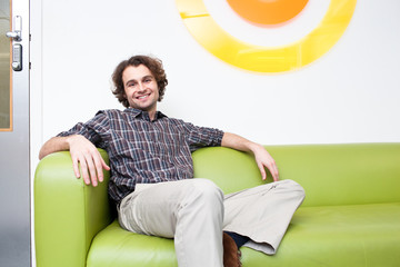 Smiling young man sitting on couch in office