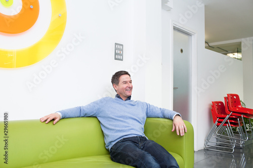 Smiling man sitting on couch in office