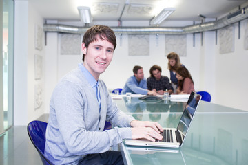 Man in conference room working on laptop with people in background