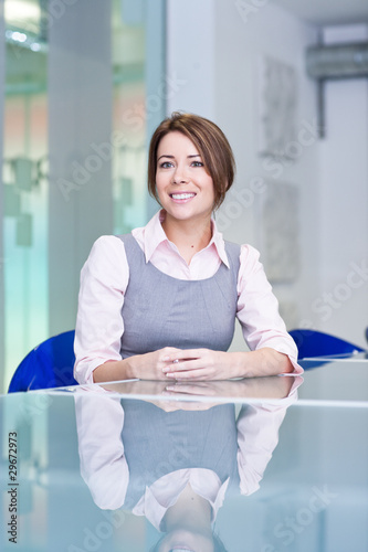 Smiling businesswoman sitting at conference table