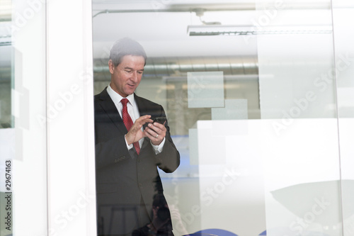 Businessman text messaging in office