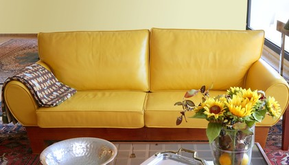 Yellow leather sofa interior sunflower bouquet