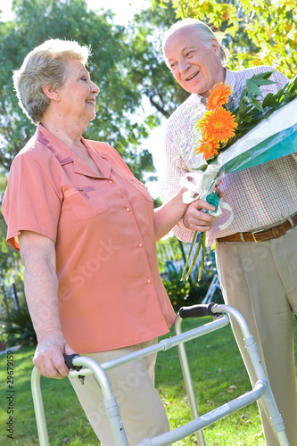 Old man giving a bouquet of flowers to a woman