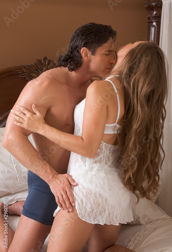 Sensual heterosexual couple in lingerie on bed