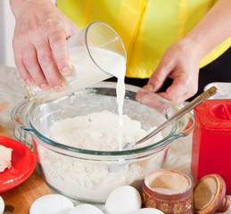 cook hands pouring milk into flour