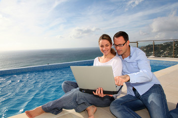 Happy couple using laptop computer by swimming-pool