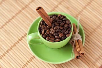 Coffee beans and cinnamon stick in a green cup