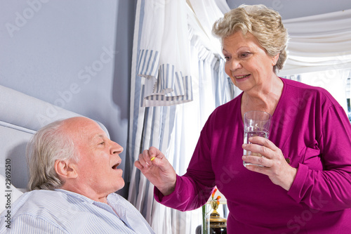 Woman giving pills to a man