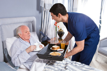 Offering breakfast to old senior man