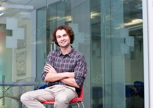 Smiling man sitting on chair in office
