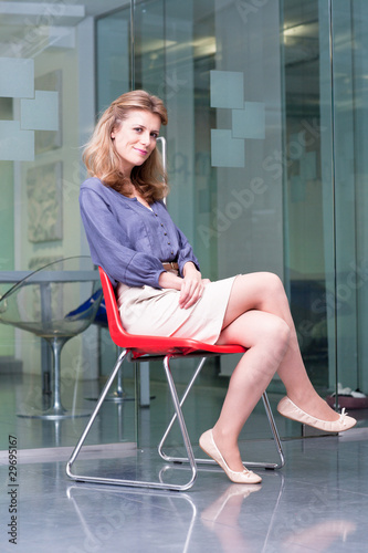 Smiling woman sitting on chair in office