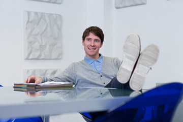 Young man in office thinking with feet on table