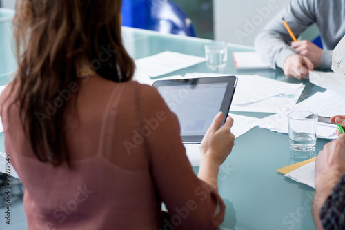 Woman using tablet computer in business meeting