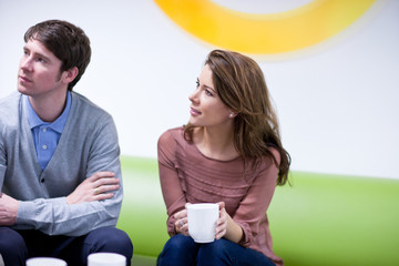 Man and woman sitting on couch in office