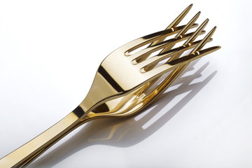 Two gold  forks isolated over white background.