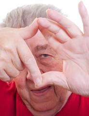 Senior schaut glücklich durch Hände